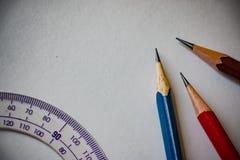 Blyertspennor och en linjal på grå bakgrund arkivbild