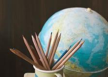 Blyertspennor och jordklot för gammal skola, tillbaka till skolabakgrund royaltyfri bild