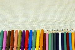 Blyertspennor och markörer i en rad på det texturerade tyget arkivbilder