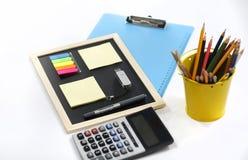 Blyertspennor, penna, minneslistablock, skrivplatta och räknemaskin royaltyfri foto