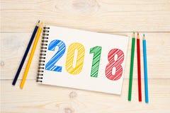 2018 blyertspennor som kläcker text i anteckningsbok Royaltyfri Fotografi