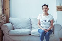 Blyg asiatisk volontär som sitter på den hemtrevliga soffan arkivbild