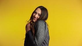 Blyg flörtkvinna som flörtar och poserar på gul bakgrund