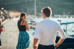 Blyg flirty kvinna som ler till en man Man att ge en komplimang till en inbunden övergående kvinna Motta en komplimang på gatan o royaltyfri bild