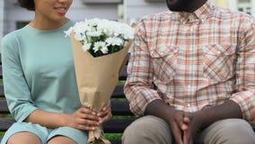 Blyg man som ger blommor till den härliga flickan, angenäm gåva på det första datumet som är floristic lager videofilmer