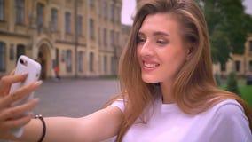 Blyg och nätt caucasian flicka med långt hår som tar selfies med hennes apparat på den stads- sikten, solig dag arkivfilmer