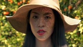 Blyg stående av den asiatiska kvinnan le först men därefter i en orange fruktträdgård som bär en hatt lager videofilmer