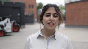 Blygsam ung flicka med mörkt hår som går i gatan och le för sommar stock video