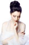 Blygsam ung kvinna med stängda ögon som isoleras på vit iklädd studiobakgrund udden av organza Royaltyfri Foto