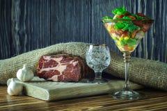 Blygsamt köttmellanmål med grönsaksallad i ett exponeringsglasvinexponeringsglas till ett skott av vodka på en grå träbakgrund 1  royaltyfria foton