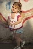blygt barn Flickan åldrades 2-3 år med hårflätade trådar eller hästsvansar som står nära en kulör stenvägg Fotografering för Bildbyråer