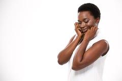 Blygt gulligt afrikansk amerikankvinnaanseende och trycka på henne kinder royaltyfri fotografi