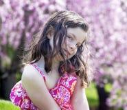 Blygt liten flickasammanträde i en trädgård Royaltyfria Bilder