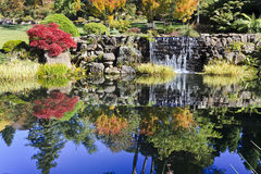 BM Bot Park Pond. National park autumn colours reflection in water pond with blue sky and streaming waterfall red yellow leaves sunny day Stock Photos