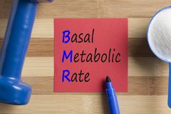 BMR Basal metabolic rate written on note. With creatine and dumbbell. Acronym. Health concept Stock Images