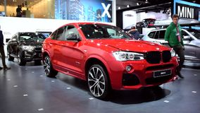 BMW X4 crossover SUV car. Man inspecting a red BMW X4 crossover SUV car on display at the 2015 Brussels Motor Show. He opens the driver's door and engine bonnet stock video