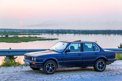 BMW E30 324d. NOVYY URENGOY, RUSSIA - JULY 26, 2013: Motor car BMW E30 324d at the roadside at the background of the sunset Stock Image