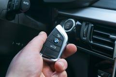 BMW X5 F15起动汽车钥匙在开始/停按钮附近的一只男性手上 现代汽车内部细节 发动引擎的钥匙 免版税库存照片