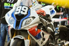 MAGNY-COURS / FRANCE - APRIL 19, 2013: BMW S1000rr HP4 at Bol d`Or 24h. BMW 24h-Endurance Racebike standing in pit in front of box royalty free stock photography