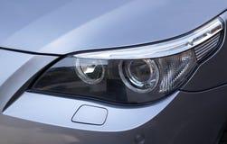 BMW Headlight. Headlight on a silver metallic BMW Stock Image