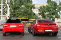 Kiev, Ukraine; June 25, 2013; BMW M6 and Audi A3 on the road in heavy rain. Back view royalty free stock images