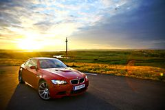 BMW M3. Bucharest, Romania - July 3, 2013: A BMW M3 car drives through a beautiful scenery, at sunset. The BMW M3 is a high-performance version of the BMW 3