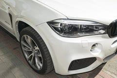 BMW X5 M Perfomance 轮胎和合金轮子 车灯 一辆白色现代豪华跑车的正面图 免版税库存图片