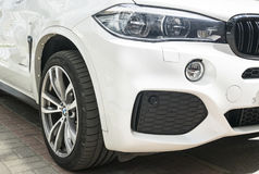 BMW X5 M Perfomance. Tire and alloy wheel. Headlight. Front view of a white modern luxury sport car. Car exterior details. Sankt-Petersburg, Russia, July 21 royalty free stock photography