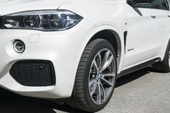 BMW X5 M Perfomance. Tire and alloy wheel. Headlight. Front view of a white modern luxury sport car. Car exterior details. Sankt-Petersburg, Russia, July 21 royalty free stock photos