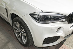 BMW X5 M Perfomance. Tire and alloy wheel. Headlight. Front view of a white modern luxury sport car. Royalty Free Stock Image