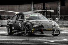BMW negro que deriva en el asfalto mojado Fotografía de archivo libre de regalías