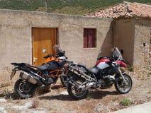 BMW R1200GS和KTM在希腊冒险1050在一个外屋旁边 免版税图库摄影