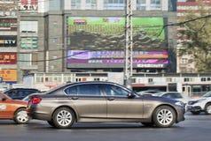BMW 7 serie i det upptagna centret, Peking, Kina Arkivbilder