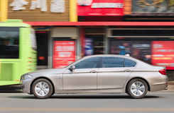 BMW 5 series longwheel base in city center, Wenzhou, China. WENZHOU-CHINA-NOV. 19, 2014. BMW 5L series on the street. German Audi, BMW and Mercedes-Benz maintain royalty free stock image