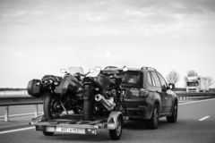 BMW suv X5 driving fast on French highway with trailer. Nice, France - May 7, 2016: Rear view of BMW suv X5 driving fast on French highway with trailer holding royalty free stock photos