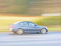 BMW traveling fast  in the countryside. A panned image of a BMW saloon  car speeding along a country road Stock Photos