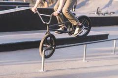 Bmx沿路轨的车手幻灯片在前轮 青少年做在bmx自行车的把戏 BMX概念 免版税库存图片