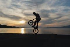 Bmx做把戏的骑自行车的人剪影反对日落 免版税图库摄影