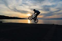 Bmx做把戏的骑自行车的人剪影反对日落 免版税库存图片