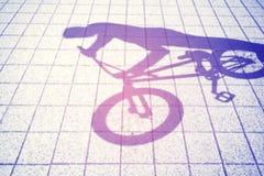 骑bmx自行车的少年的减速火箭的被定调子的被弄脏的阴影 库存照片