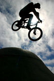 BMX air on spine ramp. BMX rider does air over spine ramp at skate park Royalty Free Stock Photography