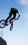 BMX bicycler over ramp. Young  boy is jumping with his BMX Bike at the skate park Royalty Free Stock Photography