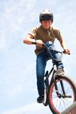BMX bicycler on  ramp. Young man  riding on a BMX bicycle on a ramp over blue sky background Stock Photo