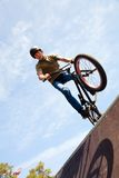 BMX bicycler on  ramp. Young man  riding on a BMX bicycle on a ramp over blue sky background Royalty Free Stock Photo