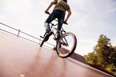 BMX bicycler on  ramp. Young man  riding on a BMX bicycle on a ramp over blue sky background Stock Photos