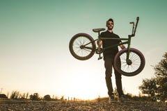 Bmx bike rider in a sunset. Guy riding a bmx bike royalty free stock image