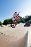 BMX Bike Stunt bar spin. Bmx rider performing a bar spin to a quater pipe ramp on a skatepark Stock Image