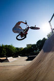 BMX Bike Stunt bar spin. Bmx rider performing a bar spin to a quarter pipe ramp on a skatepark royalty free stock photo
