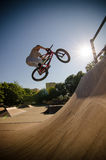 BMX Bike Stunt bar spin. Bmx rider performing a bar spin to a quarter pipe ramp on a skatepark Stock Image