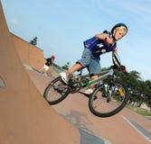 BMX Biker. Young boy jumping/ riding a BMX bike Stock Image